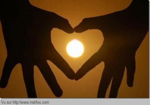 Couché de soleil dans un coeur fait par des mains